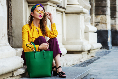 Picture of a lady sitting down on a pavement with fashionable clothing learnt in TaF.tc's Color and Style