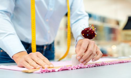 A student from TaF.tc learning how to do basic alteration on a pink fabric through the skills learnt in Basic Alteration Techniques.