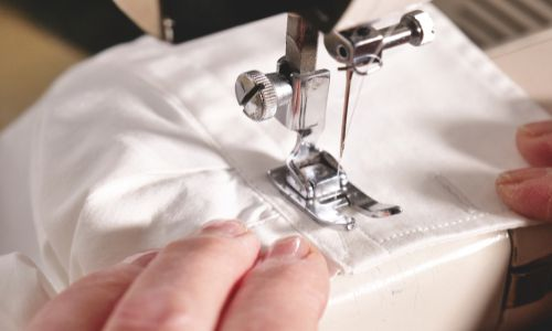 Close view of a sewing machine sewing on a white fabric in the Intermediate Drafting and Sewing class