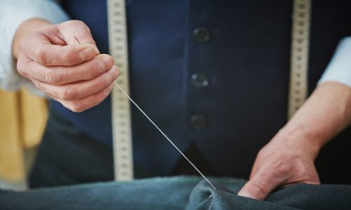A man hand-sewing on a navy fabric through the skills learnt in Intermediate Alteration Techniques