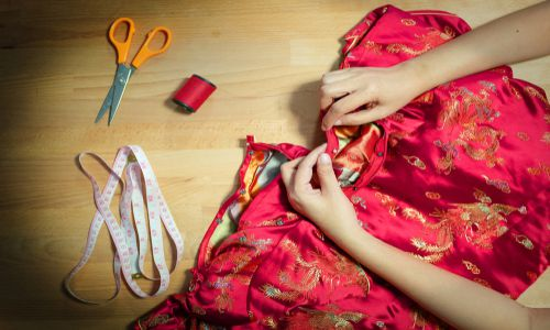 A student from TaF.tc learning how to sew the zipper portion of a silk red fabric in Heritage Apparel (Cheongsam) class