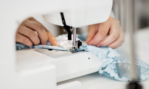 A person using a white domestic sewing machine sewing on a light blue lace fabric with the advanced skills learnt from Advanced Alteration Techniques