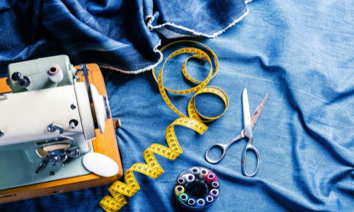 An overlay of white domestic sewing machine with sewing equipment over a blue denim fabric in the fit evaluation and pinning for alteration class.